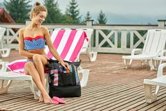 Hot girl getting sunblock cream from black backpack. stock photography