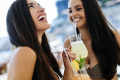 Hot girls having fun on the bech. And drinking cocktails Stock Photography