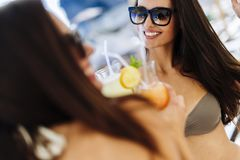 Hot girls having fun on the bech. And drinking cocktails Royalty Free Stock Photo