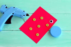 Hot glue gun. A cap from a plastic bottle, buttons, cardboard sheet, a plastic eye - set for making children's crafts Royalty Free Stock Photo
