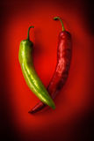 Hot green pepper on a red background Stock Photography