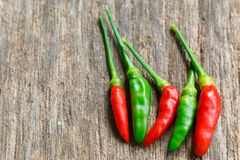 Hot green and red chili on old wood Royalty Free Stock Photos