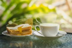 Hot green tea with biscuits on the table and a reflection mirror.  Royalty Free Stock Image