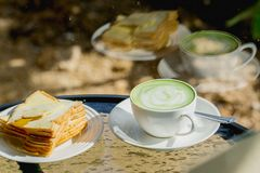 Hot green tea with biscuits on the table and a reflection mirror.  Royalty Free Stock Photo