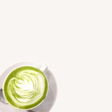 Hot green tea. Green tea in a cup of hot milk white glass Royalty Free Stock Photo