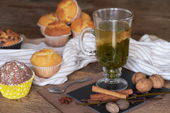 Hot green tea and fresh muffins on a wooden table. Stock Images