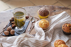 Hot green tea and fresh muffins on a wooden table. Royalty Free Stock Images
