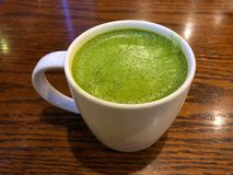 Hot green tea latte in mug. On the wood table royalty free stock photos