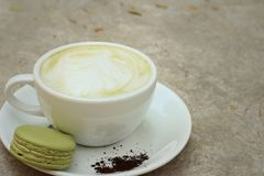Hot green tea with macaroons at coffee shop. Royalty Free Stock Image