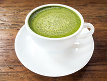 Hot green tea matcha latte cup with white saucer on wood texture. Background Royalty Free Stock Image