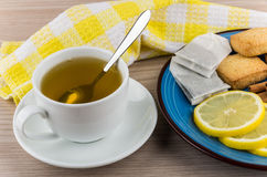 Hot green tea and plate with slices of lemon, cinnamon Stock Photos