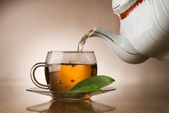 Hot tea. Hot green tea pouring in to cup close up stock photography