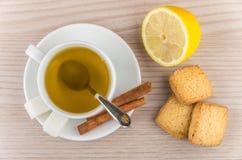 Hot green tea, sugar and cinnamon, lemon and shortbread cookies Royalty Free Stock Image