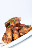 Hot grilled chicken wings on white. Plate with drizzle of sauce with copyspace Stock Image