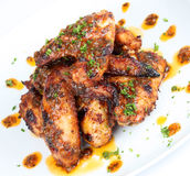 Hot grilled chicken wings on white plate. With drizzle of sauce Royalty Free Stock Photo