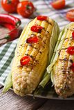 Hot grilled corn with chili peppers close-up. vertical Stock Images