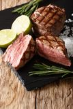 Hot grilled filet mignon steak with lime and rosemary close up. Hot grilled filet mignon steak with lime and rosemary close up on the board. vertical stock image