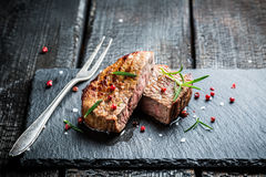 Hot grilled meat with fresh rosemary ready to eat. On burnt table Stock Photos