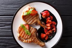 Hot grilled tasty pork chop with balsamic strawberry close-up on. A plate on a table. horizontal top view from above royalty free stock photos