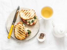 Hot grilled tomatoes, spinach, mozzarella sandwiches and green tea - healthy breakfast, snack on a light background royalty free stock photo