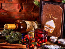 Hot grog on brick wall and card menu background. Warming grog with bottle of white wine . Label on bottle of wine. Bottle lying on winter berry. Ginger snap in Stock Images