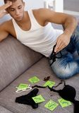 Hot guy matching names with underwear. Hot young guy matching girls names on post-it notes with female jewelry accessories and underwear stock photos