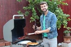 Hot guy preparing dinner in barbecue Stock Photo