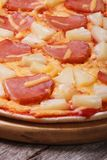 Hot Hawaiian pizza with pineapple an old wooden table Stock Photography