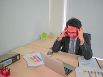 Hot Head business man very angry sitting on his desk royalty free stock photography