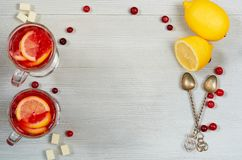Hot healthy winter drink - detox cranberry tea or sangria with fresh lemon slices in glasses on the gray concrete background. Top view with copy space for text stock photos
