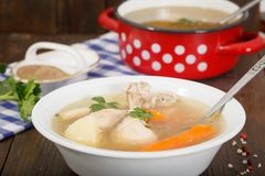 Hot homemade chicken soup in white bowl. Alternative remedy for cold and flu. Red pot with soup in background on wooden table royalty free stock image