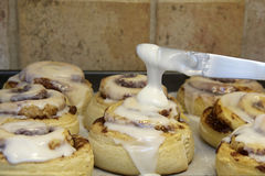 Hot homemade cinnamon rolls fresh out of the oven. Knife applying glaze frosting to buns Stock Photo