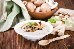 Hot homemade mushroom soup and bowl with fresh raw mushrooms. On wooden table Stock Image