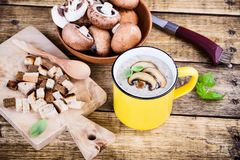 Hot homemade mushroom soup and bowl with fresh raw mushrooms. On wooden table Stock Photo