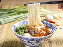 Hot instant noodles with cube beef and herbs on the table Stock Image