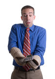 Hot Investment Concept. Concept image of a young businessman using oven mitts to handle his hot investment, isolated against a white background Royalty Free Stock Images