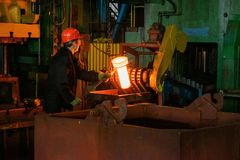 Blacksmith processes the iron product under a huge press, forging metal, stamping. stock image