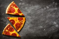 Hot italian pepperoni pizza slice on black stone. Top view. Copyspace royalty free stock image