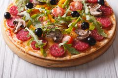 Hot Italian pizza with herbs, salami and vegetables Stock Photography