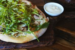 Hot Italian pizza with mushrooms and arugula on a thick dough on a wooden table in a cafe. Lunch or dinner. Shut. Copy space. stock photo