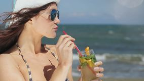 Hot lady enjoying exotic cocktail, long drink, vacation at luxury resort's beach. Stock footage stock video