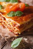 Hot lasagna with basil and tomatoes on an old table, vertical Stock Photos
