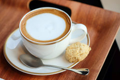 Hot latte and almond cookie. In wooden plate Royalty Free Stock Image
