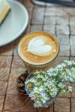 The hot latte art coffee with cake. In coffee shop stock images