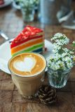 The hot latte art coffee with Colorful cake. In coffee shop stock images