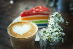 The hot latte art coffee with Colorful cake. In coffee shop stock image