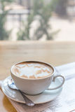 Hot latte art coffee cup with newspaper on wooden table, vintage Stock Image
