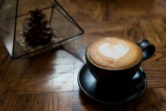 Latte art Coffee on wooden table. Hot Latte art Coffee in a cup on wooden table with copy space for text. Heart shape milk foam made by professional barista Royalty Free Stock Photo