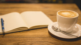 Hot latte art coffee cup on wooden table and note book, vintage Royalty Free Stock Photo