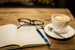 Hot latte art coffee cup on wooden table and note book, vintage Stock Photos
